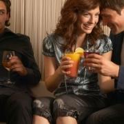 muž s pohárom v ruke sa žiarlivo pozerá ako si dvojica pripíja