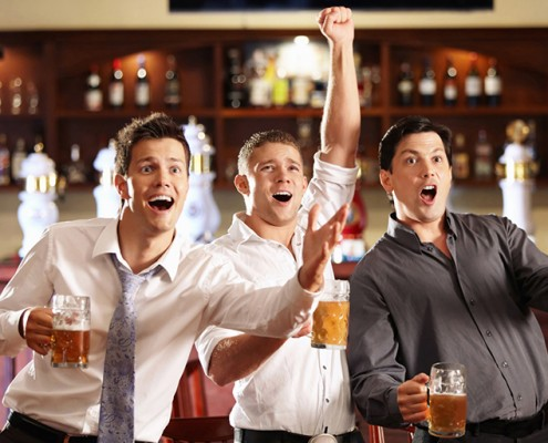 chlapi v bare sledujú zápas