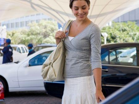 žena sa usmieva a dotýka sa auta