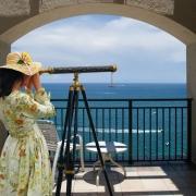 žena hľadá lásku cez ďalekohľad na dovolenke pri mori
