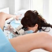 žena leží na gynekologickej koze a lekárku ju prehliada mikroskopom