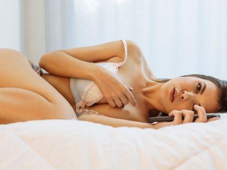 žena v spodnom prádle leží na posteli