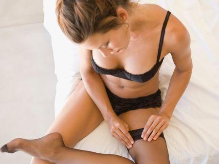 žena v čiernom erotickom prádle sedí na posteli a naťahuje si pančuchu