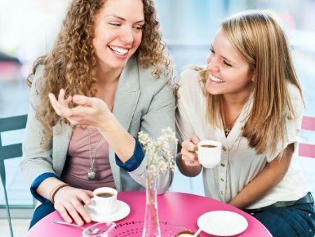 dve ženy pijú kávu a smejú sa