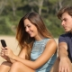 muž pozerá cez plece žene do mobilu žiarlivo