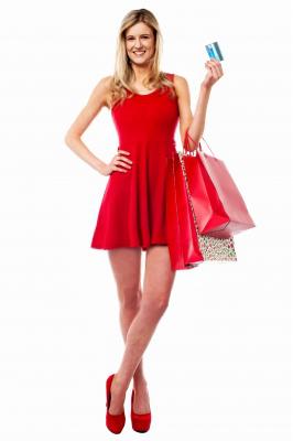 žena s kreditkou v ruke a splnými nákupnými taškami