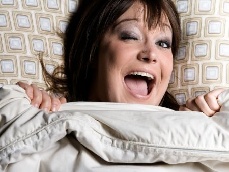 žmurkajúca zrelá žena v posteli