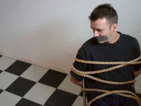 zviazaný muž na stoličke s páskou na ústach